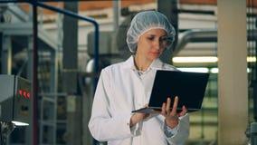 Den snygga kvinnan i likformig fungerar en bärbar dator i en fabrik lager videofilmer