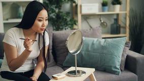 Den snygga unga kvinnan målar ögonbryn genom att använda skönhetsmedel och borsten som ser därefter, i spegel och att le Flickan  stock video