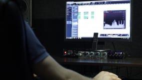 Den solida teknikern som arbetar i inspelningstudion lager videofilmer