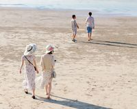 Den soliga dagen, baksidasikten av två unga kvinnor i långa klänningar och hattar strosar längs den sandiga stranden arkivfoto