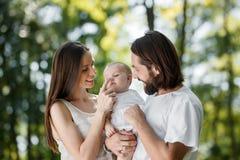 Den soliga morgonen i de iklädda härliga föräldrarna för skogen rymmer den vita tillfälliga kläderna deras lilla dotter in royaltyfri foto