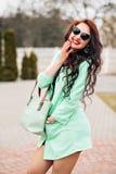 Den soliga positiva ståenden av den sexiga bedöva flickan i den korta bightklänningen som har gyckel på gatan, glädje, lycka, til Fotografering för Bildbyråer