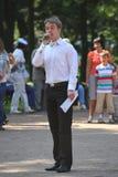 Den soliga sommardagen i staden parkerar Den ledande underhållaredansshowen i Petrovsky parkerar Talar in i mikrofonen Royaltyfri Bild