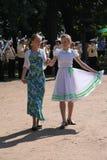 Den soliga sommardagen i staden parkerar offentliga underhållare för flickor som dansar med turistfolket under musiken av en mili Arkivbilder