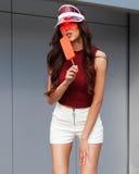 Den soliga ståenden av en asiatisk flicka i en moderiktig sommardräkt, den trendiga röda brätteskärmhatten tycks om av glass Royaltyfria Bilder
