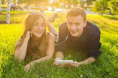 Den soliga ståenden av liggande koppla av för söta barnpar på gräset lyssnar tillsammans till musik i hörlurar på smartphonen Arkivbilder