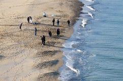 Den soliga vinterdagen folk tycker om solen på stranden royaltyfri fotografi