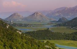 Den soluppgångskyen och floden i berg korsar dalen Royaltyfria Bilder