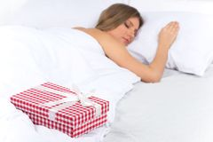 Den sovande kvinnan har den närvarande överraskningen vänta på henne i säng Royaltyfria Bilder