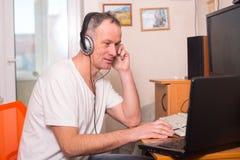 Den spända mannen i hörlurar sitter mellan en bärbar dator och en dator Arkivfoton