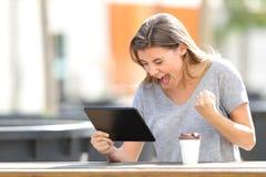 Den spännande flickan som finner online-innehållet i en minnestavla i, parkerar fotografering för bildbyråer