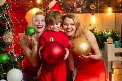 Den spännande kvinnan och den älskvärda pysen med julgarnering står vid julgranen Familj Tid nytt ?r arkivfoton