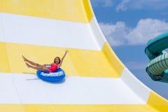 Den spännande tonårs- flickan tycker om sommarsemester i vatten parkerar att rida den blåa uppblåsbara flötet arkivbilder