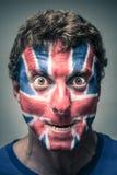 Den spöklika mannen med den brittiska flaggan målade på framsida Arkivbild