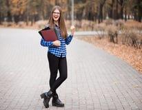 Den sp?nnande kvinnliga studenten k?nner sig upprymd fira det online-resultatet f?r segerframg?ngprestationen, den unga kvinnan s arkivfoto