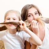 Den Spaß, der Schnurrbart schöne junge Frau und kleine blonde das Mädchen gekleidet in den weißen Hemden haben sitzen auf Sofa u. Stockfotografie