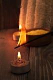 Den Spa inställningen med stearinljuset och arom klibbar på träbakgrund Royaltyfri Bild