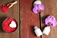 Den Spa uppsättningen på en trätabell med rött salt för bad, lotion för hud och orkidé blommar på stenar, kopieringsutrymme för d Arkivbilder