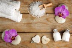 Den Spa uppsättningen på en trätabell med vitt salt för bad, lotion, handdukar och orkidén blommar på stenar Arkivbild