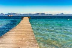 Den Spanien Majorca ön, träpir med havet och berglandskapet på fjärden av Alcudia seglar utmed kusten arkivfoton