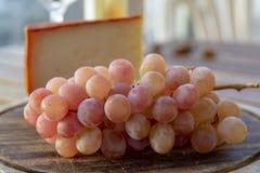 Den spanska geten mj?lkar ost med paprikabel?ggningen, och mogna rosa tabelldruvor tj?nade som med vitt vin p? utomhus- terrass fotografering för bildbyråer