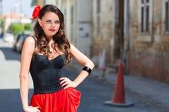 Den spanska kvinnan i svart klänning poserar i staden Royaltyfri Foto