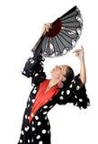 Den spanska kvinnan som dansar Sevillanas den bärande fanen, och typisk folksvart med vita prickar klär Arkivbild