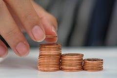 Den sparande pengarbegreppsförinställningen av den manliga handen som sätter pengar, myntar stac Royaltyfri Bild