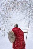 Den spartanska krigaren går i vinterskog i traditionell röd udde royaltyfri fotografi