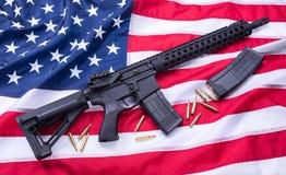 Den specialbyggda karbinen AR-15, kulor och en tidskrift på amerikanska flaggan ytbehandlar, bakgrund härlig för studiokvinna för Arkivbilder