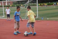 Den spela fotbollen av pojkar i mitt för shenzhen shekousportar Royaltyfri Foto
