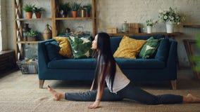 Den spensliga asiatiska idrottskvinnan är praktiserande ben-delat hemmastatt sammanträde på golvet som böjer därefter framåtrikta arkivfilmer