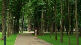Den spensliga flickan i grov bomullstvill kortsluter sommar som rollerblading stock video