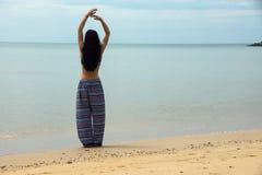 Den spensliga flickan står på stranden Arkivbild