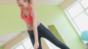 Den spensliga idrotts- flickan som gör yoga, övar inomhus sträckning lager videofilmer
