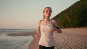 Den spensliga kvinnalöparen joggar på stranden på solnedgången eller soluppgång på havskusten lager videofilmer