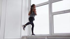 Den spensliga kvinnan gör fysiska övningar nära stort fönster lager videofilmer