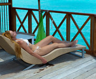 Den spensliga kvinnan har en vila på en strand Royaltyfri Foto