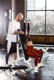 Den spensliga trevliga flickan gör en hantelbänkpress upp att sitta på en bänk, medan den idrotts- mannen försäkrar henne i den m royaltyfri foto