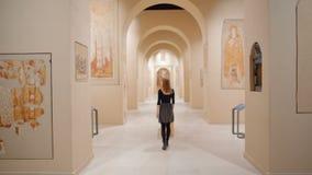 Den spensliga unga damen besöker museet och ser freskomålningen på väggar arkivfilmer