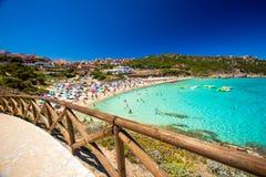 Den Spiaggia diRena Bianca stranden med rött vaggar, och azurer gör klar vatten, Santa Terasa Gallura, Costa Smeralda, Sardinia,  Royaltyfri Fotografi