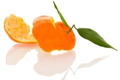 Den spiral peelen av orange mandarincitrusfrukt med gräsplan spricker ut iso Arkivfoto