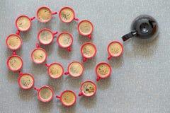 Den spiralformiga modellen av kaffe rånar och en kaffekruka Arkivbild