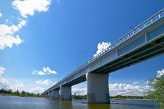 Den splitterny bron över den breda floden under blått gör klar himmel Royaltyfri Fotografi