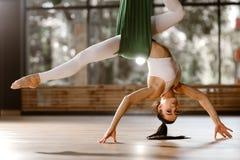 Den sportöverkanten och strumpbyxor för härlig slank mörker-haired flicka gör den iklädda vita sträcka övning på den gr royaltyfria foton