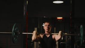 Den sportar blåste upp mannen utför lyftande vikterna som utför den stående övningen för musklerna av skuldrorna stock video