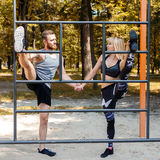 Den sportiga blonda flickan och mannen värmer upp, innan de utbildar i PA Arkivfoton