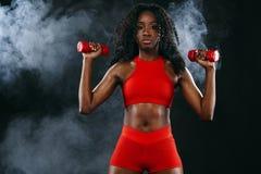 Den sportiga färdiga svarta hudkvinnan i röd sportswear, idrottsman nen med hantlar gör kondition som övar på mörk bakgrund royaltyfri foto