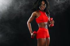 Den sportiga färdiga svarta hudkvinnan i röd sportswear, idrottsman nen med hantlar gör kondition som övar på mörk bakgrund royaltyfri bild