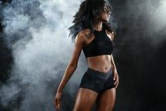 Den sportiga färdiga svarta hudkvinnan, idrottsman nen gör kondition som övar på mörk bakgrund royaltyfria bilder